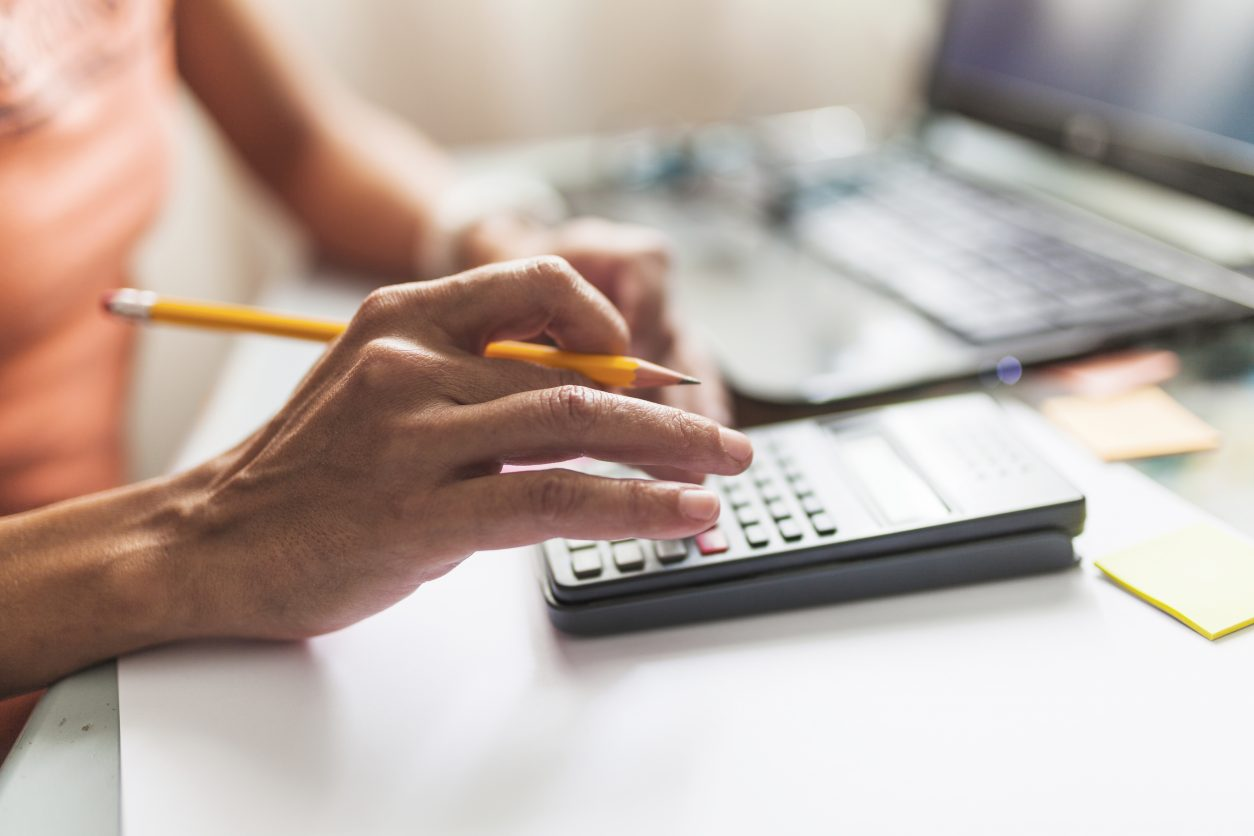 person using calculator to pay taxes