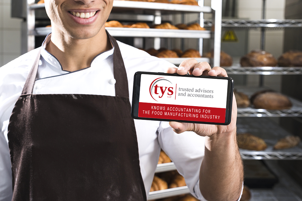Baker holding cell phone with display showing TYSLLP business card